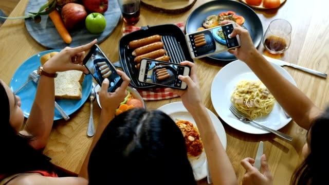 vídeos y material grabado en eventos de stock de atractivo joven asiática señoras tomar cándido foto para los medios de comunicación social y comer en ensalada, embutidos y comida italiana - compartir