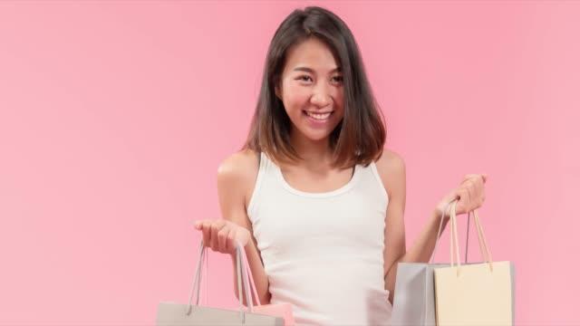 魅力的な若いアジアの女性はショッピングに満足しています。 - 通販点の映像素材/bロール