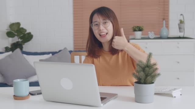 自宅のリビングルームで働いている間、親指を見せる魅力的な若いアジアの女性 - 合意点の映像素材/bロール