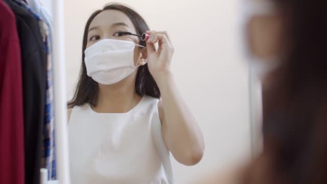 stockvideo's en b-roll-footage met aantrekkelijke jonge aziatische vrouw die beschermend gezichtsmasker draagt dat oogmake-up doet. wees mooi tijdens quarantaine - mirror mask