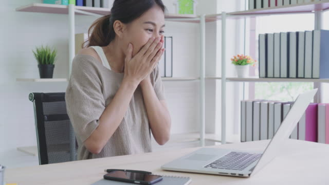 attractive young asian woman work at home looking at laptop with excited, surprise or feeling shock from good news in freelance hipster concept. - euforia video stock e b–roll
