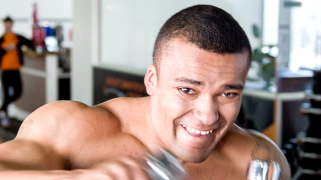 Attractive young athlete is lifting iron equipment video
