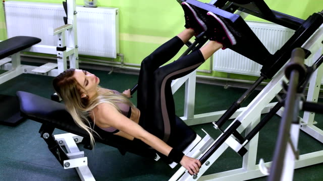 attractive young blonde woman doing strength training on a gym. pumping leg muscles. - donna forzuta video stock e b–roll