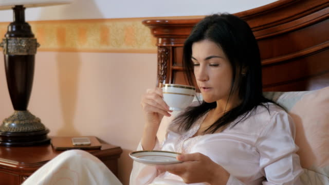 vídeos de stock e filmes b-roll de attractive young brunette drinking a tea and show a thumb in the bed - lapa