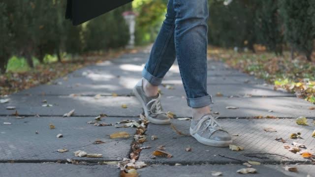 attraktiv ung affärskvinna med en portfölj i en svart jacka och glasögon steg, promenader och danser utomhus. jublar, skrattar och har kul i parken. - street dance bildbanksvideor och videomaterial från bakom kulisserna