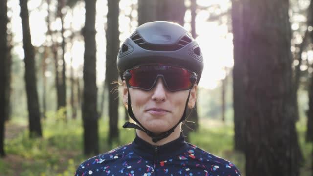 attractive young caucasian woman puts off cycling glasses wearing black helmet and jersey. triathlon concept - triatleta video stock e b–roll