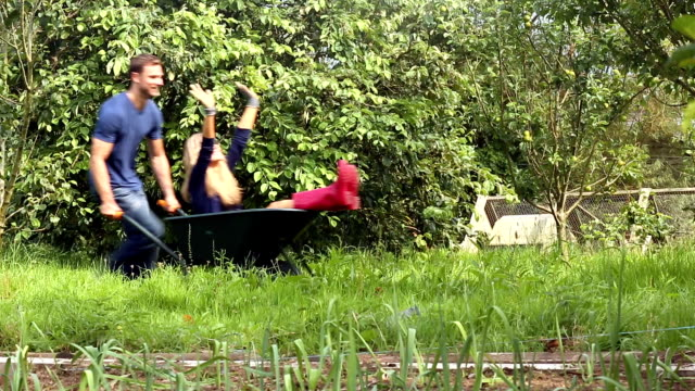 stockvideo's en b-roll-footage met attractive young couple messing around with wheelbarrow - kruiwagen met gereedschap
