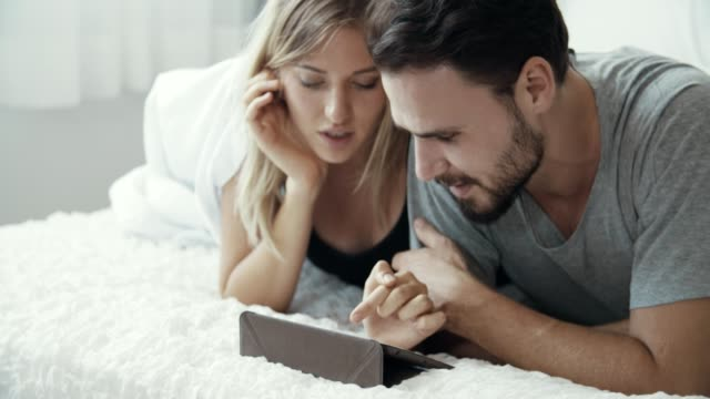 Attractive young couple watching tablet at home 4k video footage of an attractive young men checking in with his wife while she uses her tablet on the bed at home newlywed stock videos & royalty-free footage