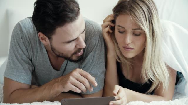 Jeune couple attirant observant la tablette à la maison - Vidéo