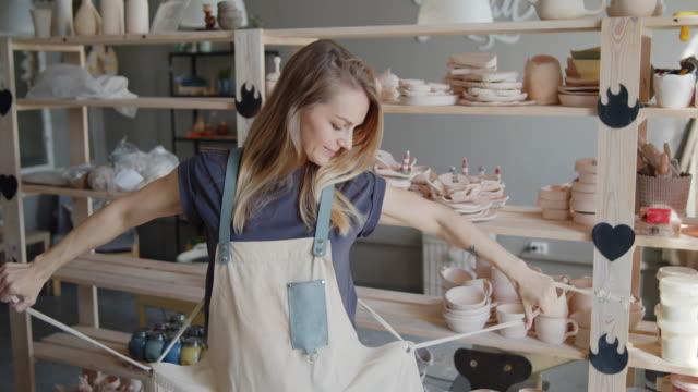 vídeos de stock e filmes b-roll de attractive young female potter putting on apron. - avental