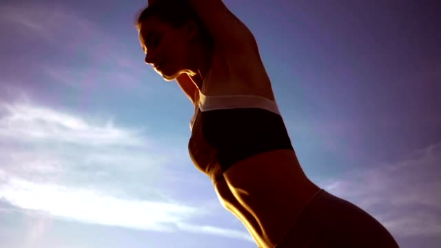Attractive young fitness strong lady at the beach make stretching exercises video
