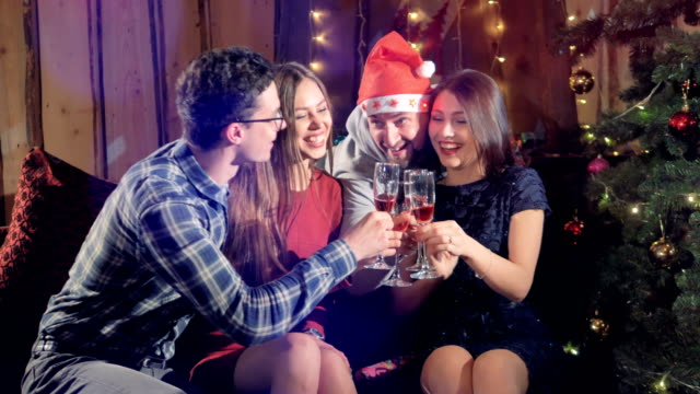 Attractive young friends celebrating xmas, new year or birthday party indoors. video