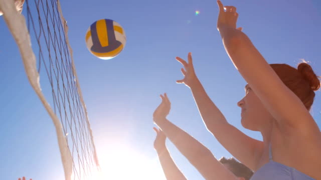 attractive young friends playing beach volleyball - volleyball stock videos and b-roll footage