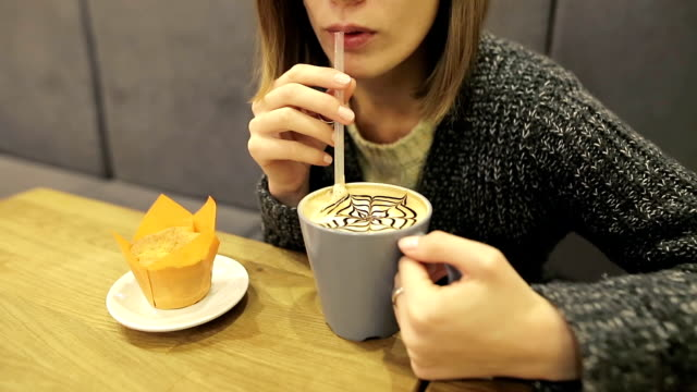 Attractive young girl in glasses drinks coffee coconut latte through a straw sitting in a cafe video