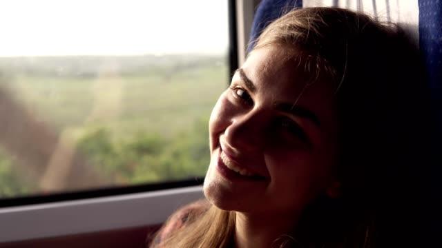 vídeos y material grabado en eventos de stock de chica atractiva y joven sonríe a la cámara. viajando en tren. naturaleza verde fuera de la ventana. la muchacha mira pensativo por la ventana. cierre para arriba - tren