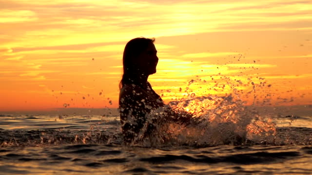 slow motion: attractive young girl playing with water in ocean at golden sunset - pesche bambino video stock e b–roll