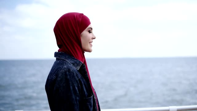 attractive young girl with hijab on her head is walking supposedly near the sea side with seagulls flying on the background - cultura del medio oriente video stock e b–roll