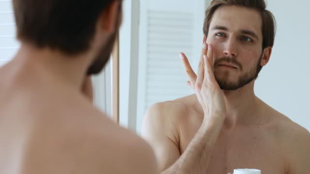 鏡を見て顔にクリームを適用する魅力的な若い男 - スキンケア点の映像素材/bロール