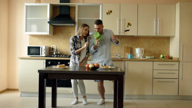 Attractive young joyful couple have fun dancing and singing while cooking in the kitchen at home video
