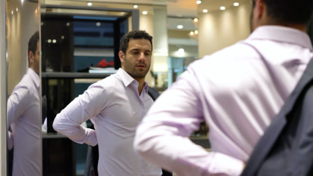 Attractive young man at a men's store trying on a suit while looking at a mirror