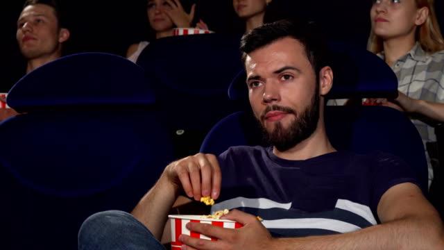 vídeos de stock, filmes e b-roll de pipoca de jovem atraente comer durante chato filme no cinema - balde pipoca