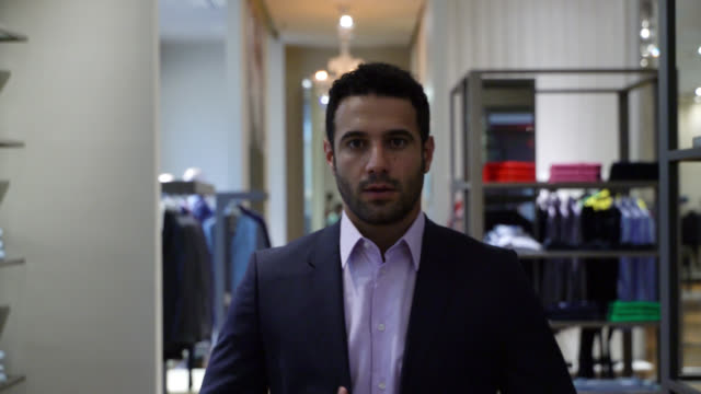 vídeos de stock e filmes b-roll de attractive young man looking at himself at the mirror while trying on a suit - espelho