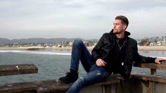 Attractive young man sitting on the edge of a pier over the ocean