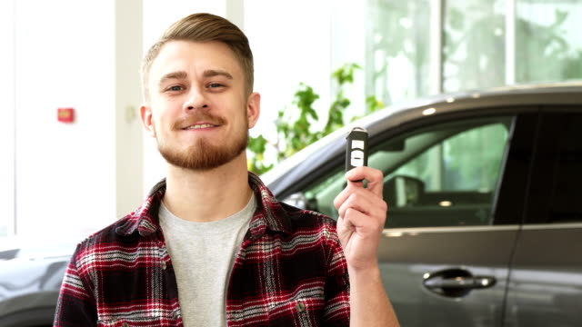 Attractive young man smiling holding car keys posing at the automotive dealership Happy young handsome bearded man smiling showing car keys to his new automobile standing at the dealership showroom ownership buying consumerism customer purchase. car key stock videos & royalty-free footage