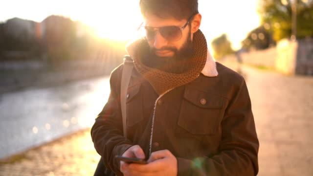 街で携帯電話を使用して魅力的な若者 - 川岸点の映像素材/bロール
