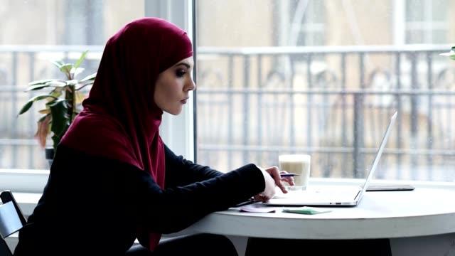 attraktiv ung muslimsk flicka med hijab använder laptop för att hitta viktig information - hijab bildbanksvideor och videomaterial från bakom kulisserna