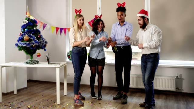 attractive young office workers opening a bottle of sparkling wine while celebrating christmas and new year in the office. happy colleagues celebrating in the office - office party stock videos and b-roll footage