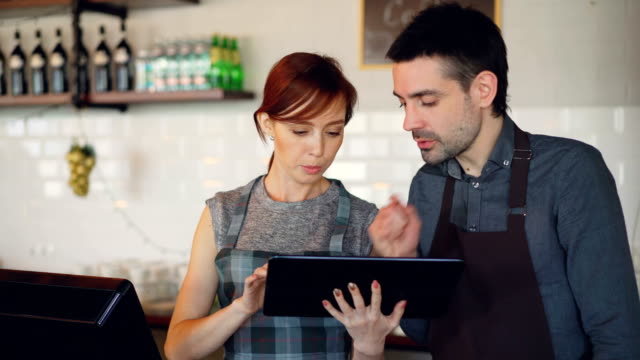 Attractive young people coffee house owners are using tablet and talking while working at counter. Partnership, successful youth and modern technology concept.