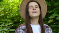 istock Attractive young pregnant woman in hat walking in green mixed forest, enjoy at breathing fresh air. Close up portrait of cheerful brunette girl smiling and rejoices warm summer day. Selective focus 1256630052