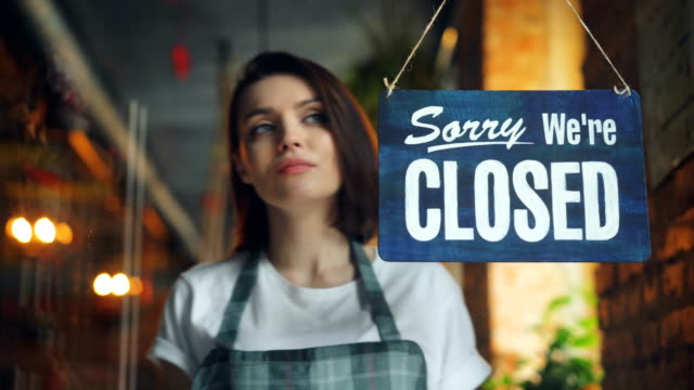 vídeos de stock e filmes b-roll de attractive young waitress changing closed to open sign on cafe door smiling - store