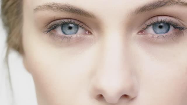 attractive young woman against white background - trattamento per la pelle video stock e b–roll