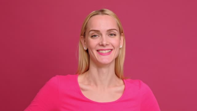 Attractive young woman blonde in a red T-shirt and jeans posing on a pink background. Shows different emotions, surprise, joy, sadness.