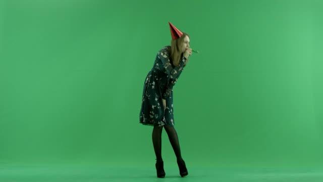 魅力的な若い女性が吹く笛、背景にクロマキー ビデオ