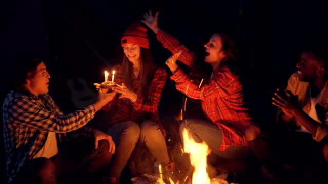 attraktive junge frau wanderer feiert geburtstag im wald immer kuchen kerzen ausblasen, während ihre freundinnen sind hände klatschten und schreien. feier und natur-konzept. - geburtstagskerze stock-videos und b-roll-filmmaterial
