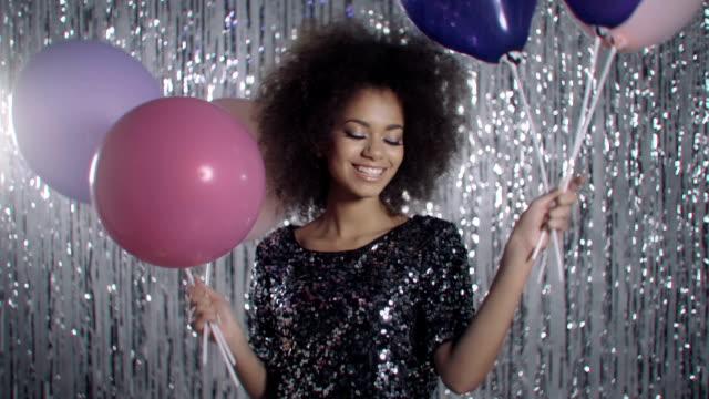 vídeos de stock e filmes b-roll de atraente jovem segurando balões em um fundo de brilho prata, a sorrir. - mulher balões