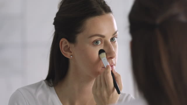 Attractive young woman holding brush apply foundation on face Attractive young woman wear dressing gown hold brush apply powder foundation on face healthy skin put cosmetics looking in mirror, happy beautiful lady doing morning beauty makeup routine in bathroom foundation make up stock videos & royalty-free footage