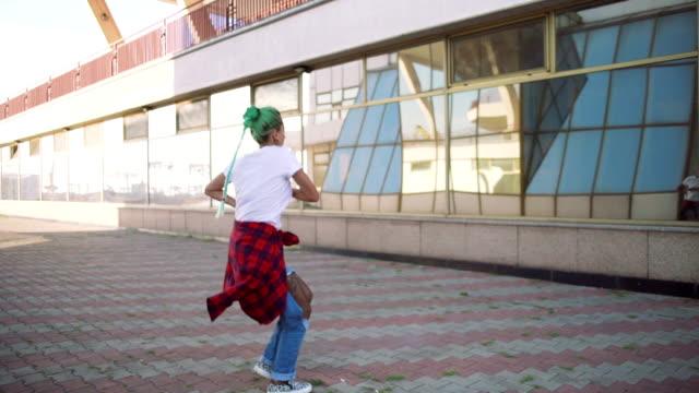 vídeos de stock, filmes e b-roll de mulher jovem e atraente em um olhar elegante e cabelo verde dançando livremente no meio urbano, velocidade lenta - bailarina