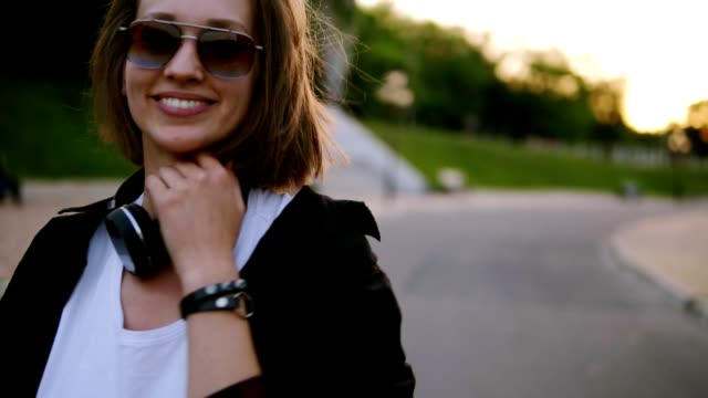 attractive young woman in a stylish outfit turns to camera and smiles seductively, continues walking away from the camera. fashionable look, sunglasses. blurred background - krótkie włosy filmów i materiałów b-roll