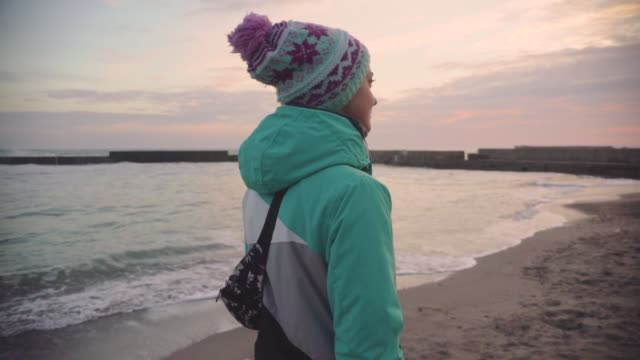 Attractive young woman in a warm jacket walking on the stone beach at sunset. Slow motion
