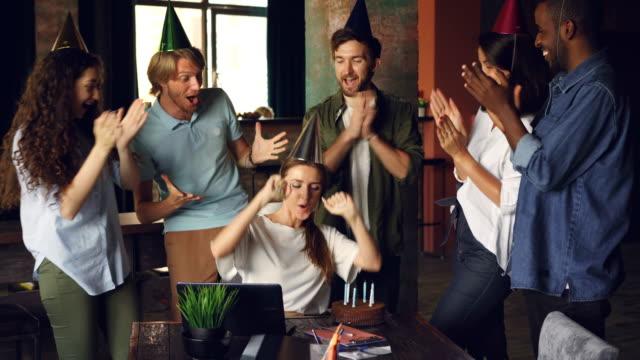 魅力的な若い女性が誕生日のケーキの上の蝋燭を吹くと笑って、彼女の同僚は、手をたたいている間彼女を祝福します。パーティーや仕事のコンセプトです。 ビデオ