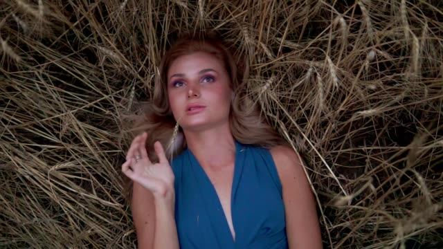 Attractive young woman laying in the golden wheat field. Her hand is touching wheat ear. Harvest concept. Harvesting. Slow motion shot video