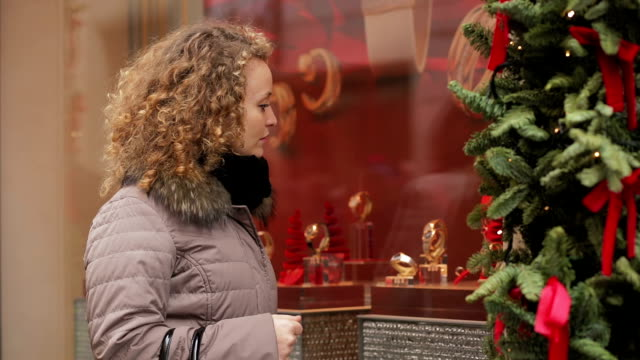 Attractive young woman looking at the shop window with christmas atmosphere video