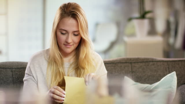 Attractive young woman opening an envelope at home video