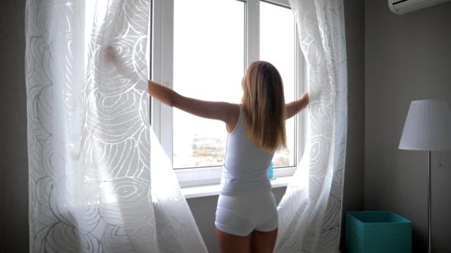 vídeos de stock, filmes e b-roll de mulher jovem e atraente abre as cortinas e aproveite a vista da cidade a partir da altura - largo descrição geral