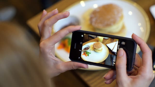 Attractive young woman Photographing food in coffee shop. closus-up video