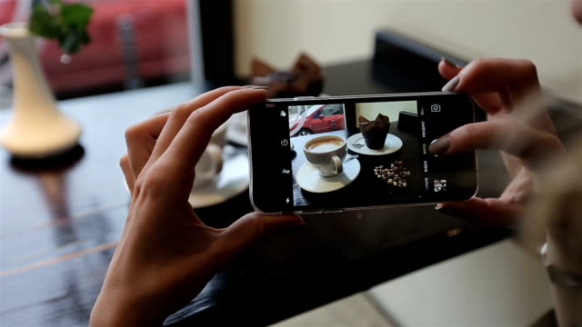 Attractive young woman Photographing food in restuarant cafe. closus-up video